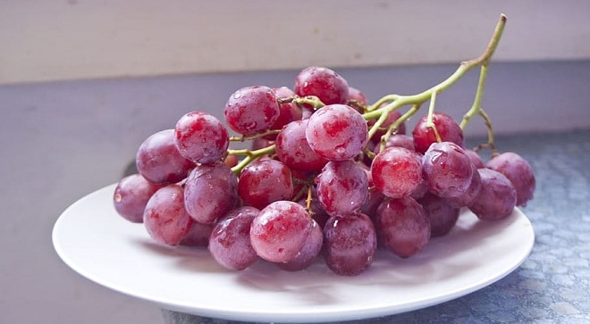 red grapes on a white plate on a marble table