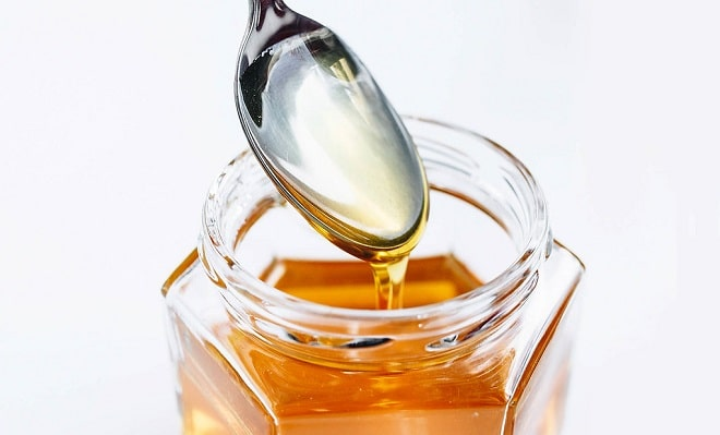 honey in a glass jar with a spoon