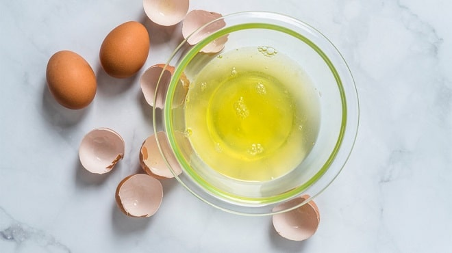 egg whites in a glass bowl with egg shells shattered across a marble table