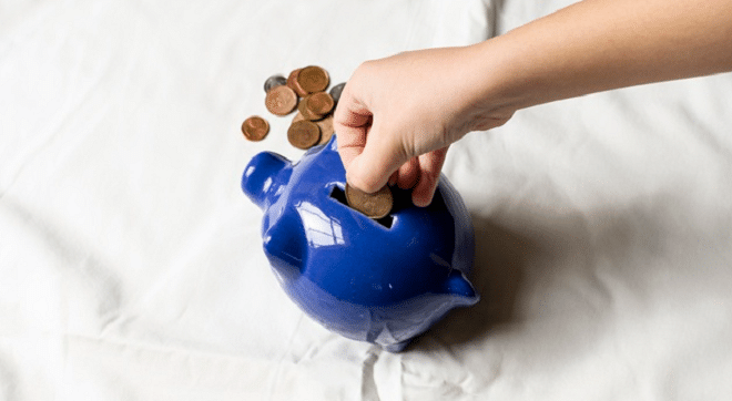 donate child putting coins into a blue piggy bank