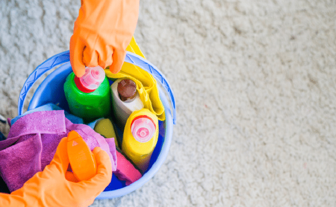 cleaning products in a blue bucket being held by a cleaner wearing orange gloves